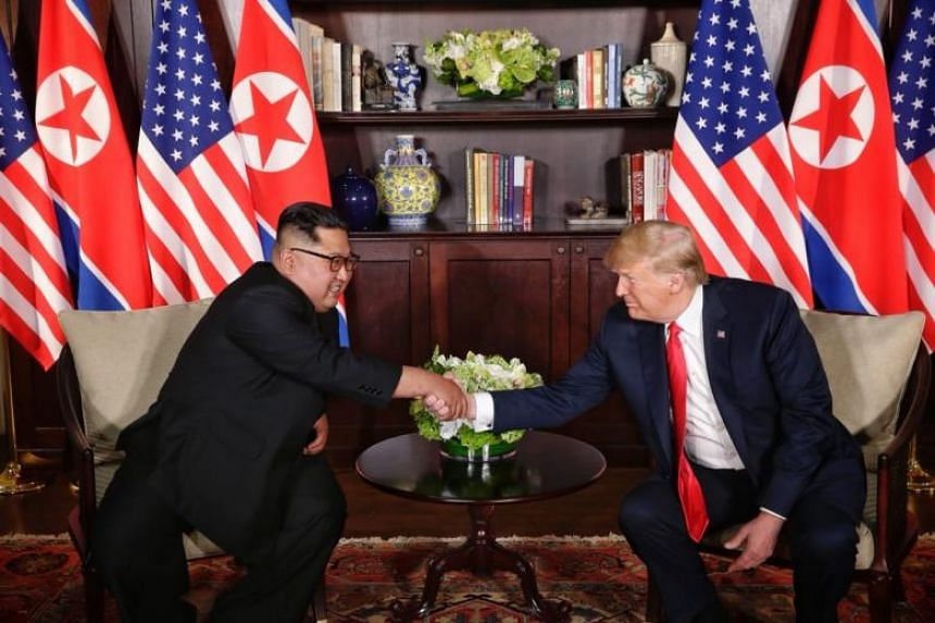 US President Donald Trump and North Korean leader Kim Jong Un shaking hands during their first one-on-one meeting at Capella Singapore, on June 12, 2018.