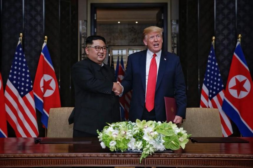 US President Donald Trump and North Kim Jong Un shaking hands after signing a joint document at Capella Singapore, on June 12, 2018.