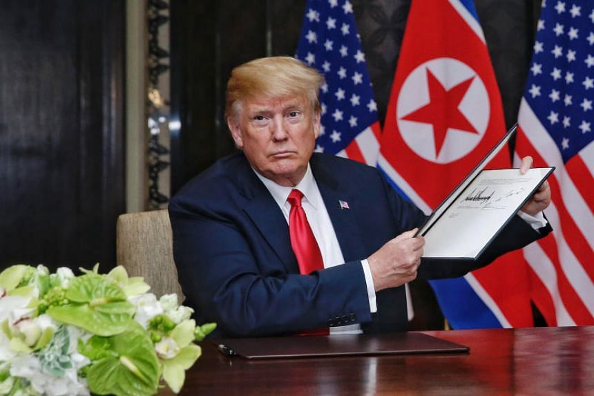 US President Donald Trump holding up an agreement signed by himself and North Korean leader Kim Jong Un at Capella Singapore on June 12, 2018.