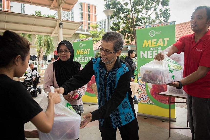Representatives from Jamiyah Singapore distributing mutton to beneficiaries at the Multi-Purpose hall beside Nee Soon Central Community Centre on June 12, 2018.
