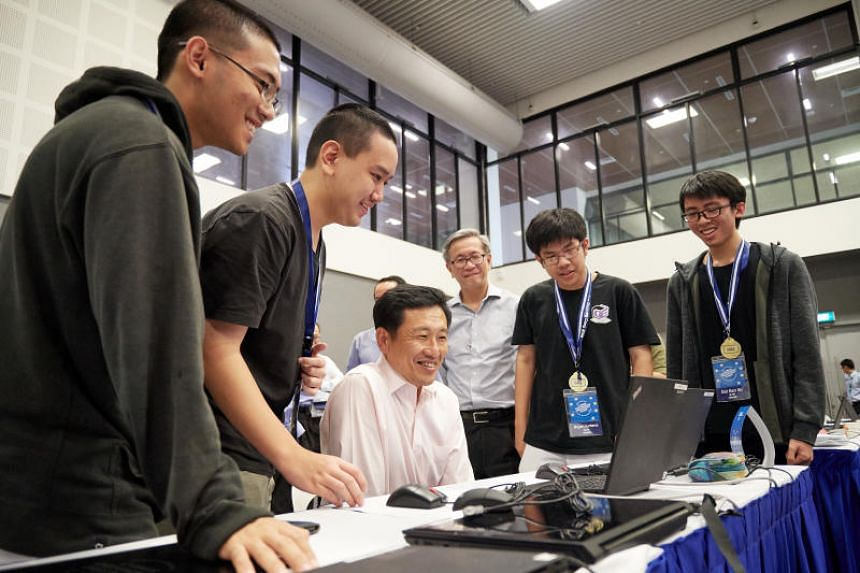 Raffles Institution students (from left) Zhang Weiyao, 17, Jaryl Ngoh Ye Shank, 18;, Bryan Juniano, 18 and Ooi Ken Jin, 17 demonstrate to Education Minister Ong Ye Kung  how they won the junior category.