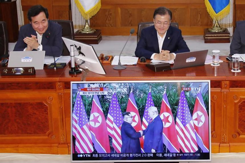 South Korean President Moon Jae In (right) and Prime Minister Lee Nak Yon (left) watch a television screen showing the summit between US President Donald Trump and North Korean leader Kim Jong Un during a Cabinet meeting at the presidential Blue Hous