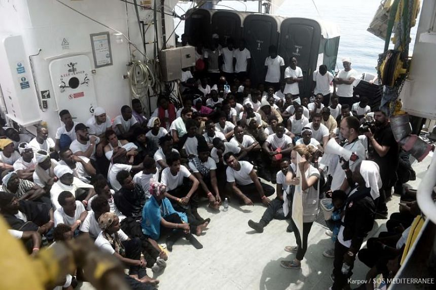 Members of the SOS Mediterranee NGO talking to rescued migrants aboard the French NGO's ship Aquarius, in the search and rescue zone in the Mediterranean sea.