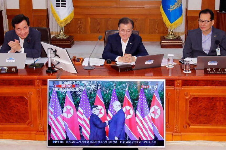 South Korean President Moon Jae In looking at a broadcast of the Singapore summit during a Cabinet meeting at the Presidential Blue House in Seoul, on June 12, 2018.