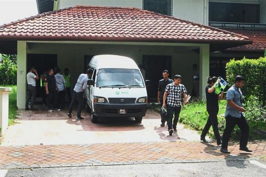 Police loading boxes into a van during the raid on a house at Precinct 10 in Putrajaya.