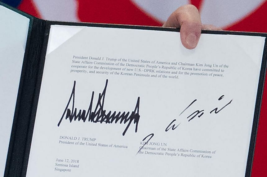 The signatures of US President Donald Trump (left) and North Korean leader Kim Jong Un are seen on a document following a signing ceremony at the Capella Singapore hotel on June 12, 2018.