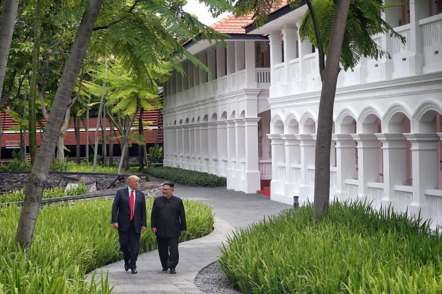 US President Donald Trump and North Korean leader Kim Jong Un strolling together through the grounds of the Capella Singapore hotel after their working lunch, during the historic summit at the hotel on Sentosa Island, on June 12, 2018.