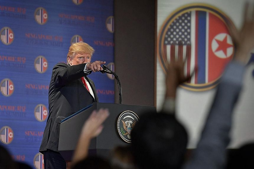 """US President Donald Trump speaking to the media after the summit yesterday. In the joint statement, Mr Trump """"committed to provide security guarantees"""" to North Korea, and Mr Kim Jong Un """"reaffirmed his firm and unwavering commitment to complete denu"""
