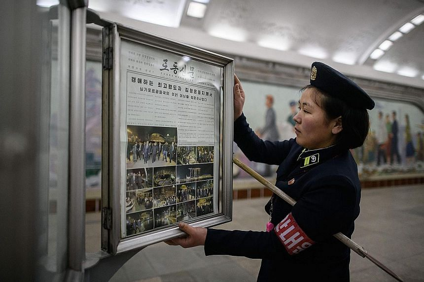 A conductor putting up the Rodong Sinmun newspaper, showing images of North Korean leader Kim Jong Un in Singapore, at a news-stand on a Pyongyang metro subway platform yesterday.