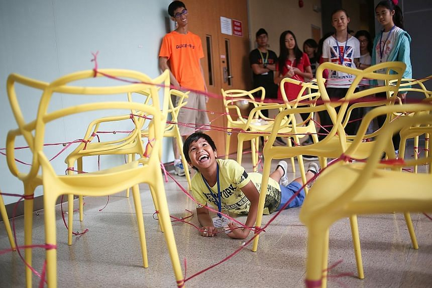 Norman Syaaqir, 11, playing a game where he navigated an obstacle course and avoided touching the chairs and the red raffia string. The event was Camp Simba, a camp for children whose families are affected by cancer. During the camp, the premises of