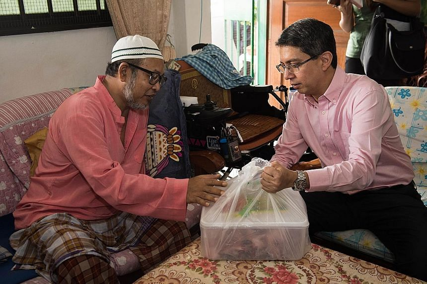 Dr Muhammad Faishal Ibrahim (right), Senior Parliamentary Secretary for the Ministry of Social and Family Development and Ministry of Education, giving fresh mutton to Mr Sulaiman Ismail during his home visit yesterday as part of the Meat For The Nee