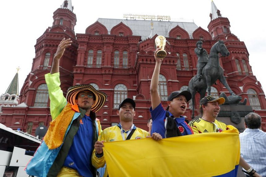 Colombian football fans cheer with a replica World Cup trophy at the State Historical Museum near Red Square, Moscow, on June 12, 2018.