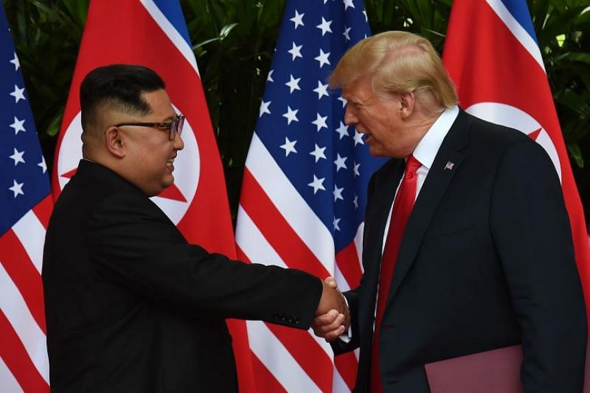North Korea's leader Kim Jong Un (left) shakes hands with US President Donald Trump after taking part in a signing ceremony at the end of their historic US-North Korea summit, at the Capella Hotel on Sentosa island in Singapore on June 12, 2018.