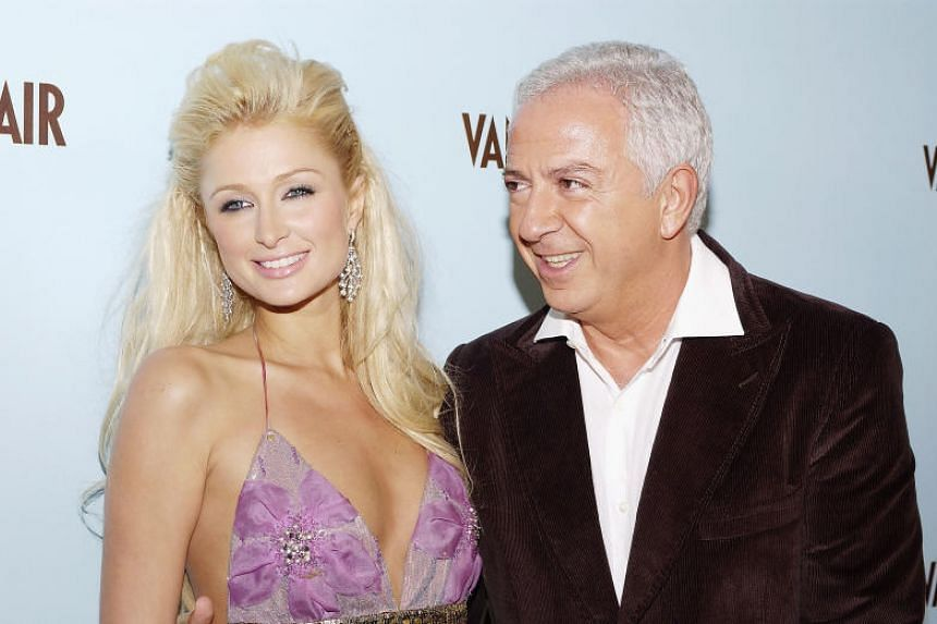 Paul Marciano with Paris Hilton in 2004. The co-founder of the Guess fashion brand has resigned in the wake of an investigation into sexual assault claims.