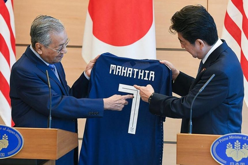 Japanese Prime Minister Shinzo Abe gave his Malaysian counterpart Mahathir Mohamad a Japan World Cup team jersey with the number 7, to show he is his country's seventh premier.