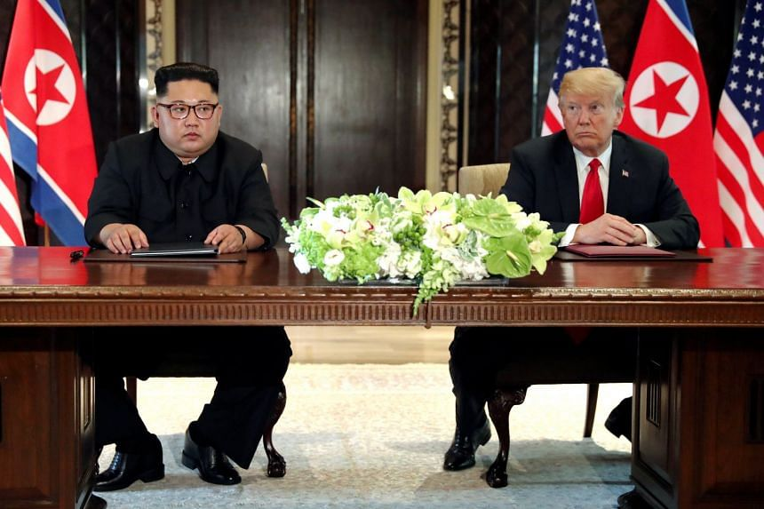 US President Donald Trump and North Korea's leader Kim Jong Un at a signing ceremony at the conclusion of their summit at the Capella Singapore hotel, on June 12, 2018.