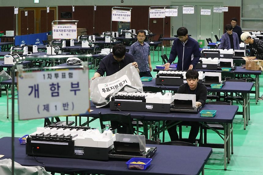 Election management officials check ballot sorters in the lead up to elections in Suwon, South Korea, on June 11, 2018.