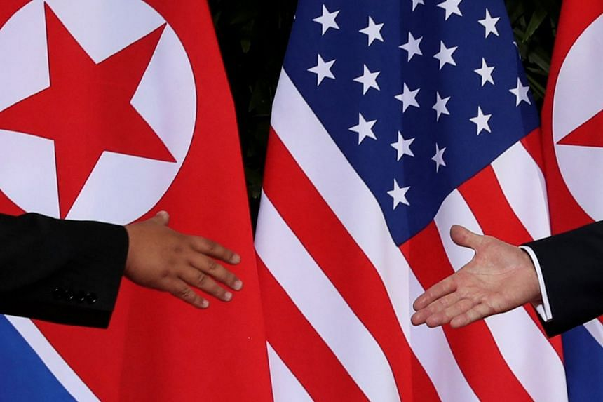 US President Donald Trump and North Korean leader Kim Jong Un reaching out for a handshake at the start of their summit at the Capella Singapore, on June 12, 2018.