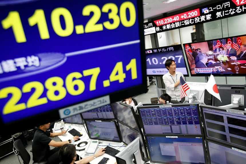 Employees of a foreign exchange trading company work near monitors screening the US-North Korea summit (centre top) and the Japanese yen's exchange rate against the US dollar (top left) in Tokyo, on June 12, 2018.