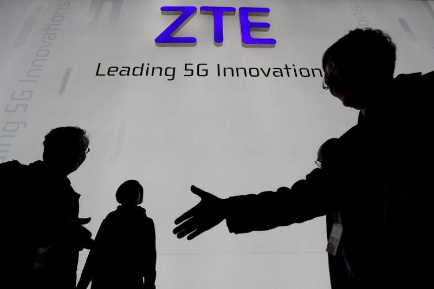 Visitors pass in front of the Chinese telecoms equipment group ZTE Corp booth at the Mobile World Congress in Barcelona, Spain, on Feb 26, 2018.