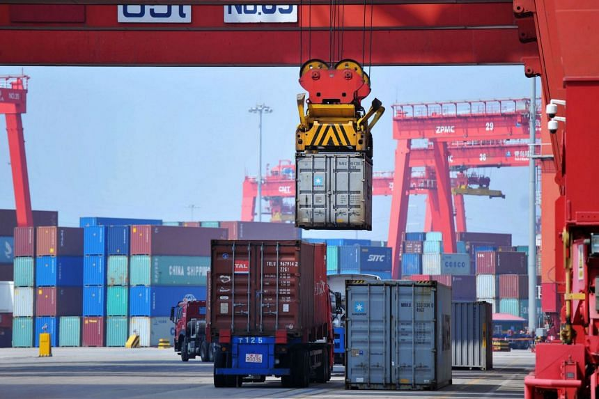 A container is transferred at a port in Qingdao in China's eastern Shandong province, on June 8, 2018.