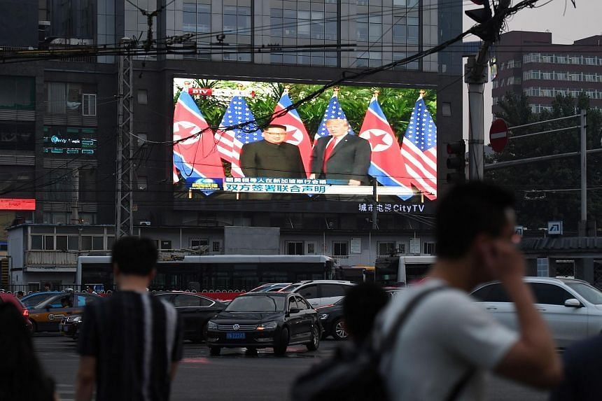 A large screen shows news footage of the Singapore summit meeting between US President Donald Trump and North Korean leader Kim Jong Un, beside a street in Beijing, on June 12, 2018.