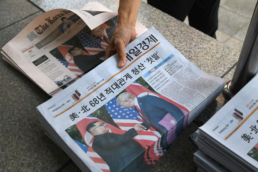 A South Korean newspaper deliveryman collects newspapers in Seoul reporting the summit between US President Donald Trump and North Korean leader Kim Jong Un, on June 12, 2018.
