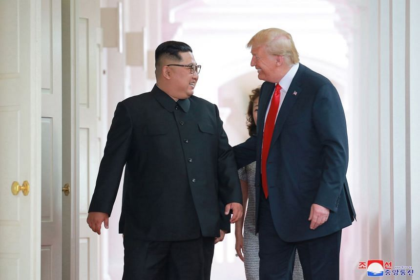 North Korean leader Kim Jong Un and US President Donald Trump walking together before their summit at Capella Singapore, on June 12, 2018.