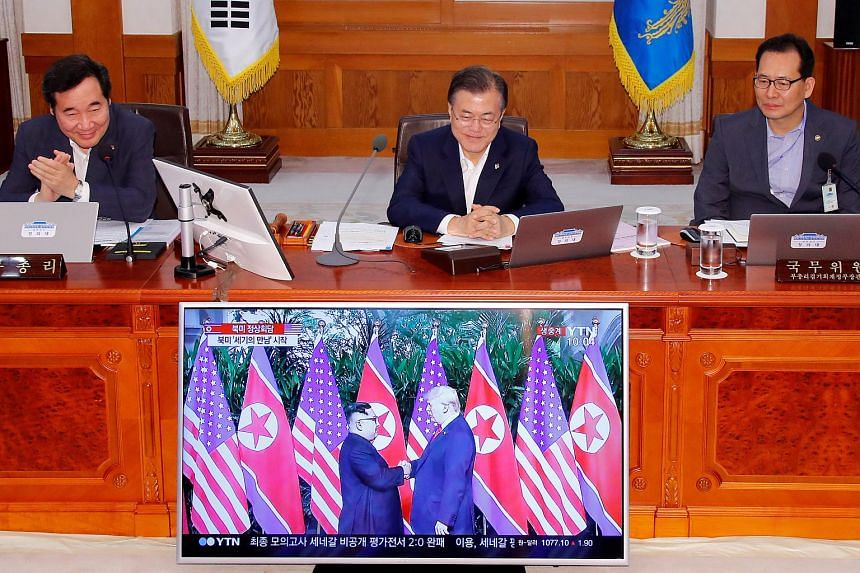 South Korean President Moon Jae In (centre) looks at a TV broadcasting a news report on summit between the US and North Korea during a cabinet meeting at the Presidential Blue House in Seoul, South Korea, on June 12, 2018.