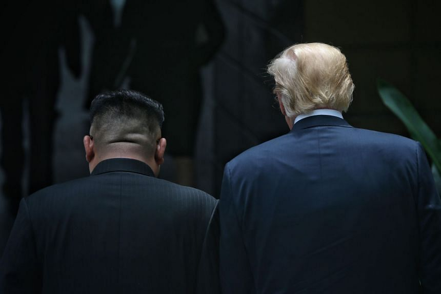 """Mr Kim and Mr Trump taking a walk in the courtyard of Capella Singapore hotel yesterday. Analysts noted that the US-North Korea declaration mentioned denuclearisation, but not the US demand of """"complete, verifiable and irreversible denuclearisation"""