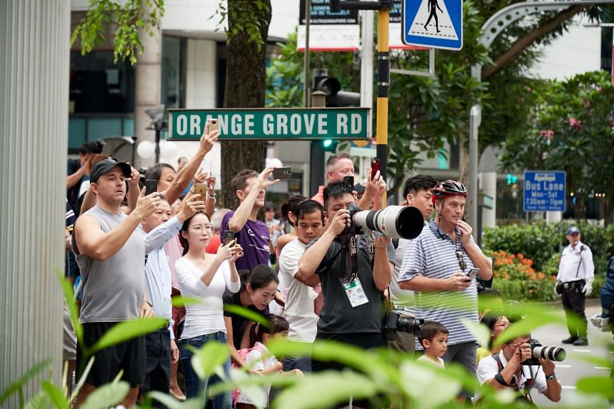 Left: Photographers and members of the public getting ready to snap pictures of Mr Kim's motorcade at the junction of Orange Grove and Orchard roads. Over the past days, crowds have gathered around the St Regis and Shangri-La, where the leaders sta
