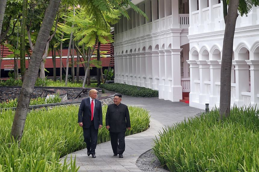 US President Donald Trump and North Korean leader Kim Jong Un strolling through the grounds of the Capella hotel after their working lunch yesterday, before they signed the historic agreement.