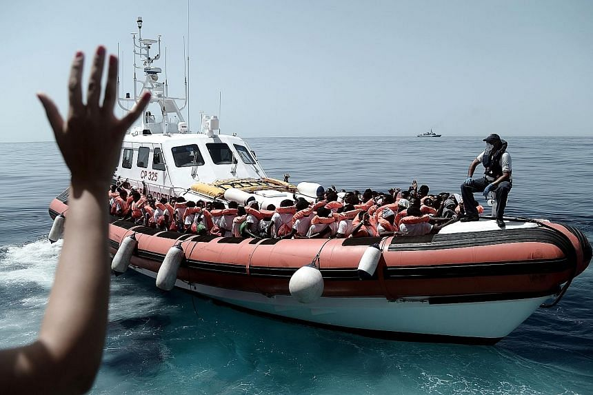 Rescued migrants and humanitarian workers on board an Italian coastguard vessel following their transfer from the French Medecins Sans Frontiers (doctors without borders) ship Aquarius. Relations between France and Italy became strained after French