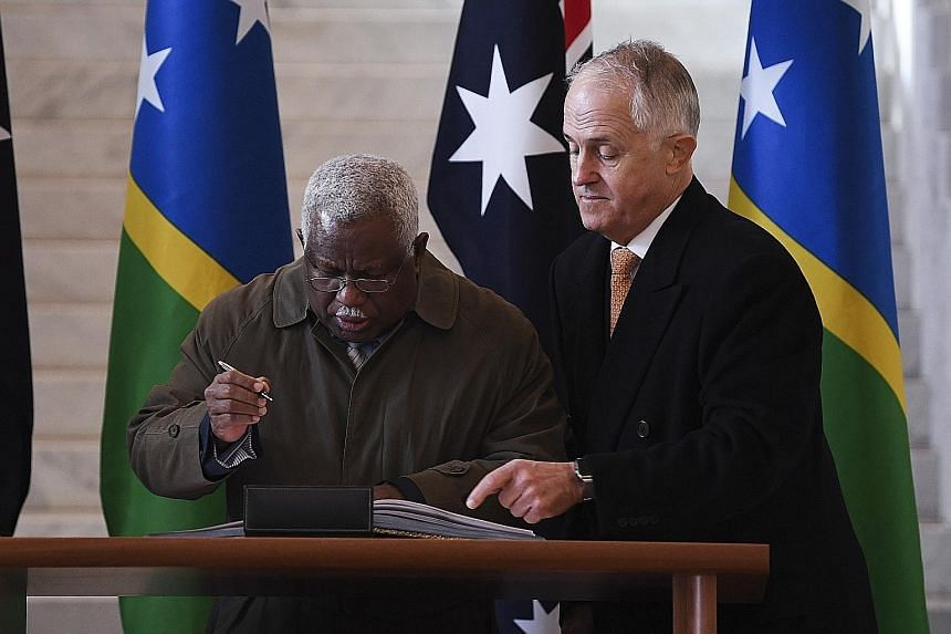 Solomon Islands Prime Minister Rick Houenipwela (left) and Australian Prime Minister Malcolm Turnbull at the signing for the undersea project. The Solomons dropped its deal with China's Huawei after Australia raised concerns.