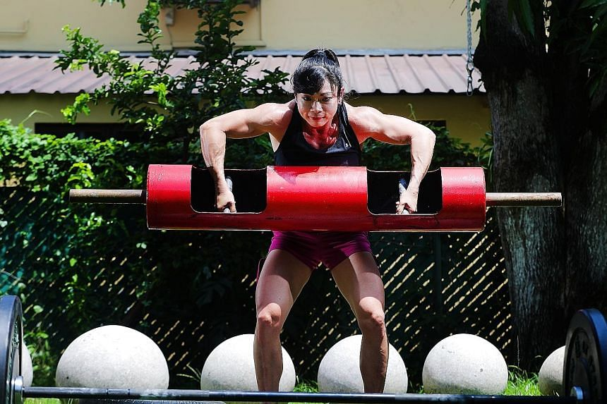 Barbara Chng lifting a log as part of her training regimen. The 43-year-old, who is also a mother of twins, won the women's Under-62.5kg category at the World Log and Deadlift Championships on the Gold Coast last month.