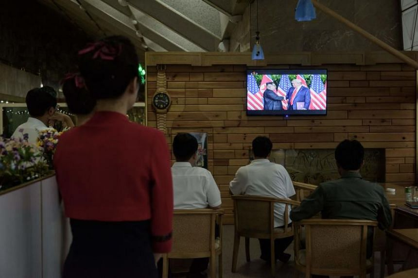 North Koreans watching a television footage of their leader Kim Jong Un attending a summit in Singapore with US President Donald Trump, in Pyongyang on June 14, 2018.