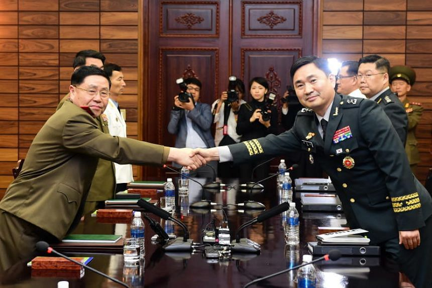 South Korea's lead negotiator Kim Do Gyun (right) shakes hands with his North Korean counterpart Ahn Il San during high-level inter-Korean military talks in the border village of Panmunjom on June 14, 2018.