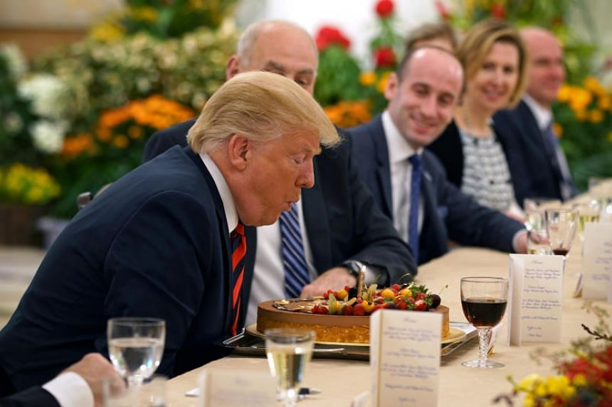 US President Donald Trump blows out the candle on his birthday cake during a working lunch with Prime Minister Lee Hsien Loong at the Istana on June 11, 2018.