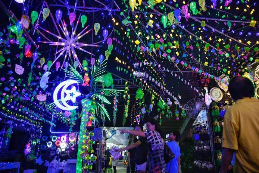 Visitors browsing a range of decorative lights at the Geylang Serai Hari Raya Bazaar on May 17, 2018.