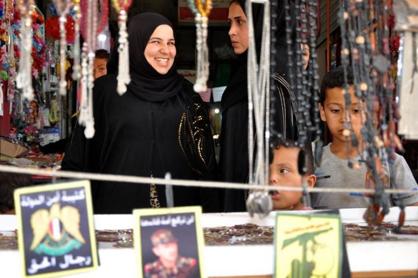 Women and children choosing ornaments at a market in Syria's north-eastern city of Hasakeh, which is open past dusk ahead of the Eid al-Fitr feast for the first time in years.