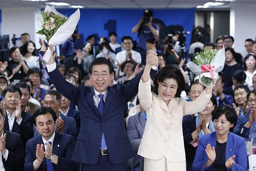 The ruling Democratic Party's Mr Park Won Soon and his wife Kang Nan He celebrating with supporters after he was re-elected mayor of Seoul for a third term on Wednesday.