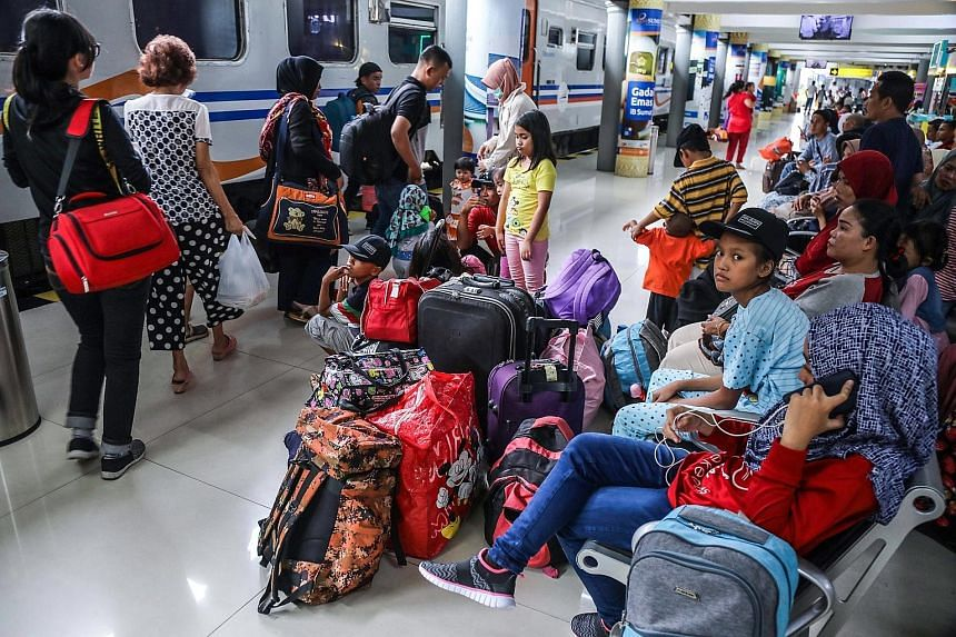 People travelling to their home villages waiting at a packed train station in Medan on Wednesday.