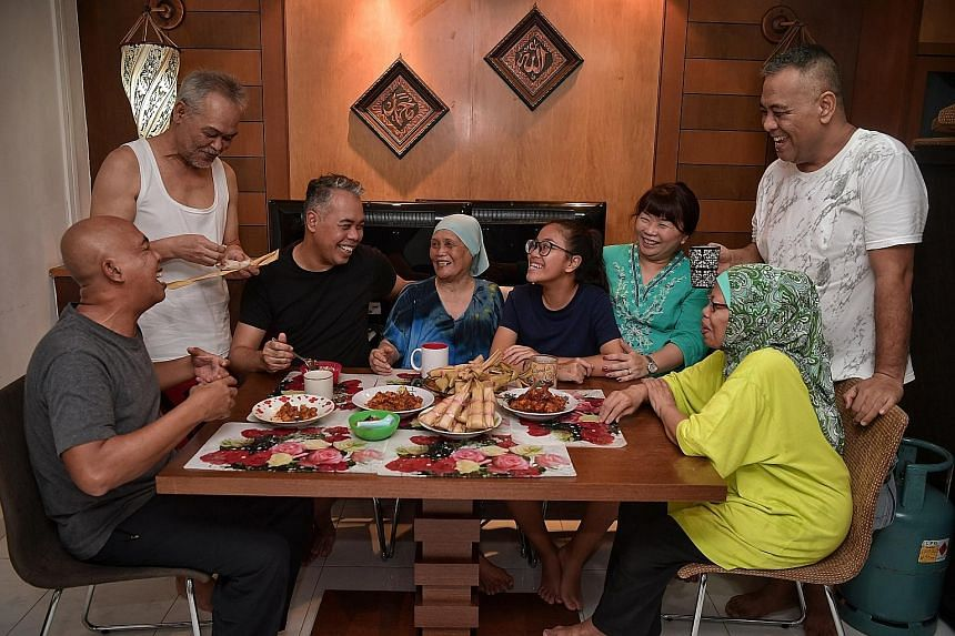 From left: Family members Omar Hashid, 59; Mohd Noor Hashid, 61; Ismail Hashid, 53; Marseah Bonoh, 84; Qurratu'aini Choi Ismail, 14; Nur Qaisarah Alya Choi, 50; Marianah Hashid, 63; and Zulkefli Hashid, 46; taking a break from the cooking yesterday.