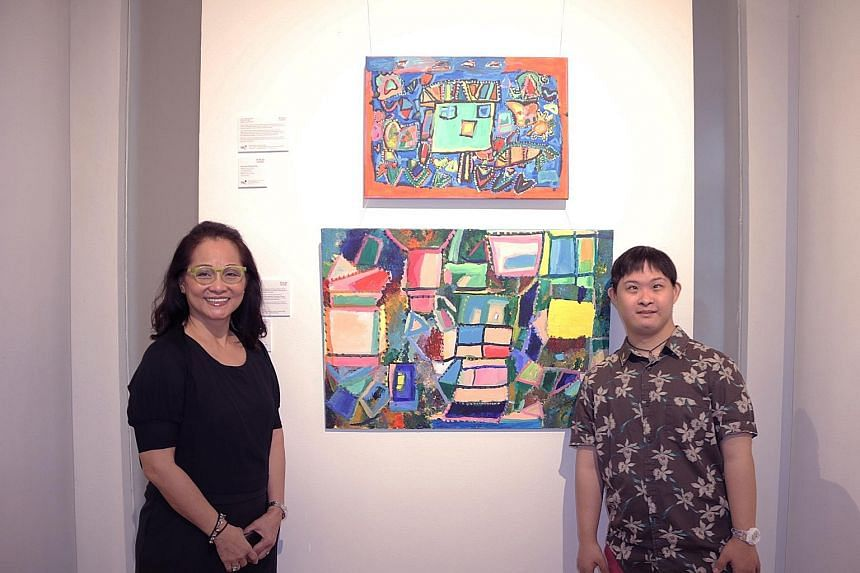 Mr Cavan Chang and his mother Cecilia Lai with his pieces at the Rhythm And Water exhibition. The 30-year-old, who has Down syndrome, enjoys creating abstract art and is keen on the new arts programme.