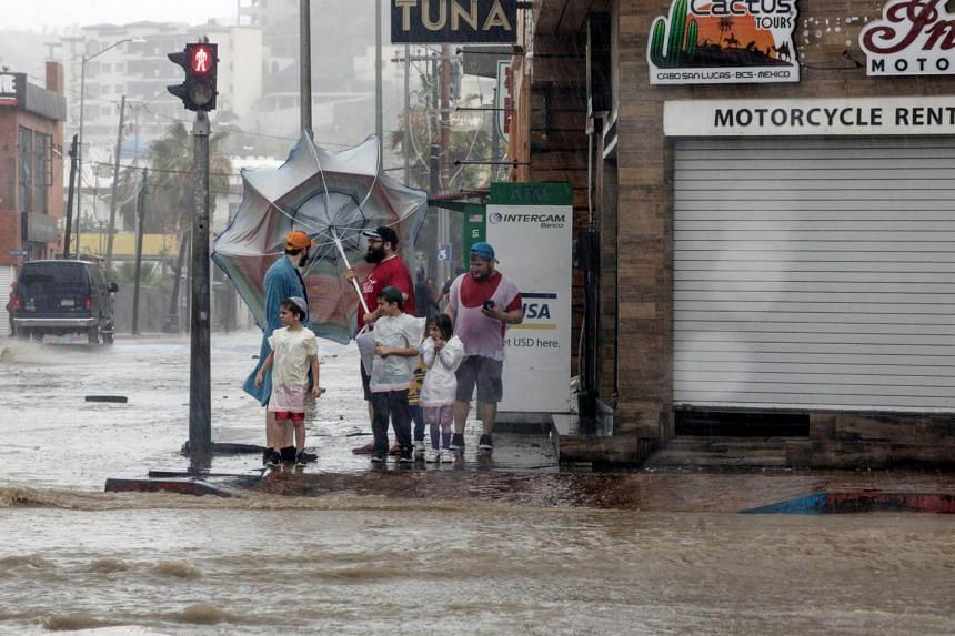 People stand near a flooded street as tropical storm Bud passes, in Los Cabos, Baja California Sur, Mexico, on June 14, 2018.
