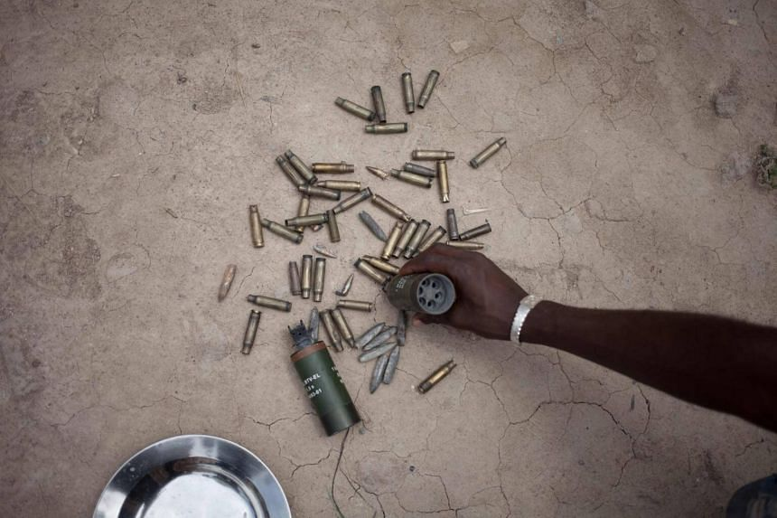 A man shows shell casings of bullets fired by the UN peacekeeping force Minusca and Central African troops in front of the base of Nimery Matar Djamous in Bangui, on April 9, 2018.