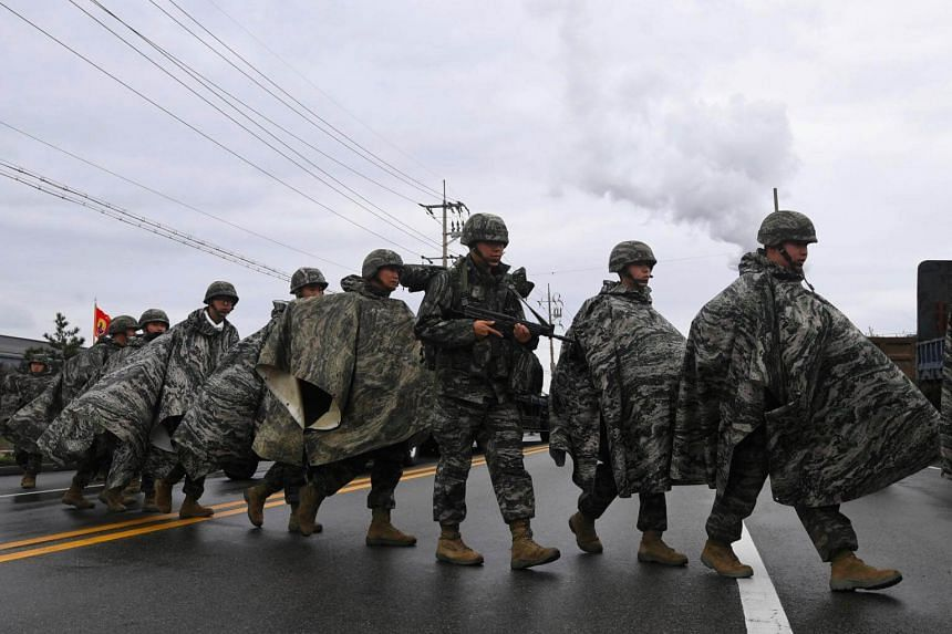 South Korean Marines cross a road after arriving at a port during a joint military exercise with the US in Pohang, on April 5, 2018.