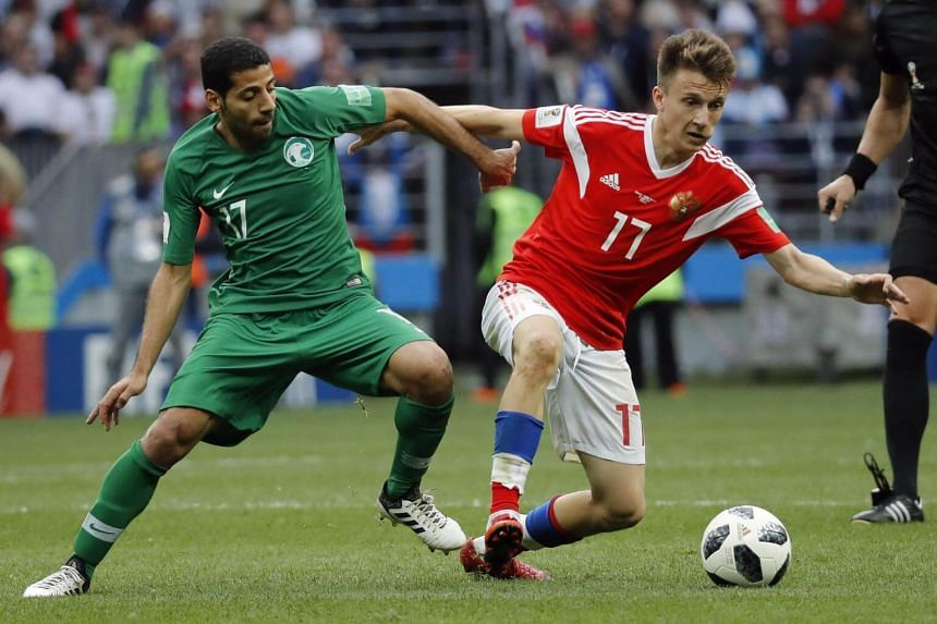 Roman Zobnin of Russia (right) and Taiseer Al Jassam of Saudi Arabia in action during the Fifa World Cup 2018 group A preliminary round football match in Moscow, on June 14, 2018.