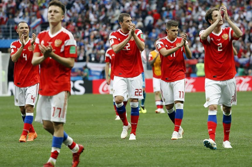 Russian players react after winning the match against Saudi Arabia in Moscow, on June 14, 2018.