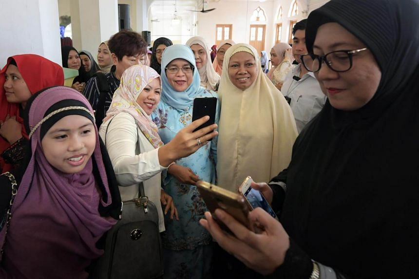 President Halimah Yacob, greets worshippers at the Sultan Mosque after the Eidulfitri prayer, on June 15, 2018.